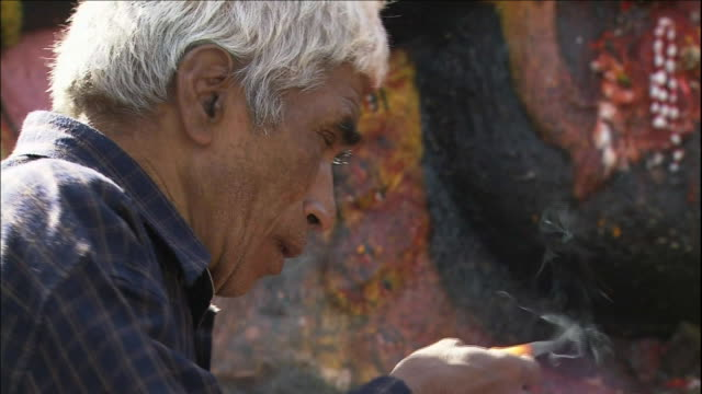 Nepalese worshiper Tilt Up Kala Bhairab Close Shot