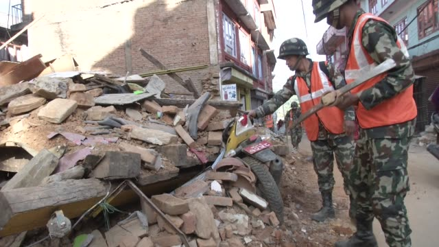 vídeos de stock e filmes b-roll de nepali army dig away at rubble on the side of the road / a major earthquake hit kathmandu mid-day on saturday, april 25th, and was followed by... - major road