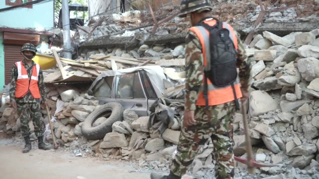 vídeos de stock, filmes e b-roll de nepali army dig away at rubble on the side of the road / a major earthquake hit kathmandu mid-day on saturday, april 25th, and was followed by... - major road