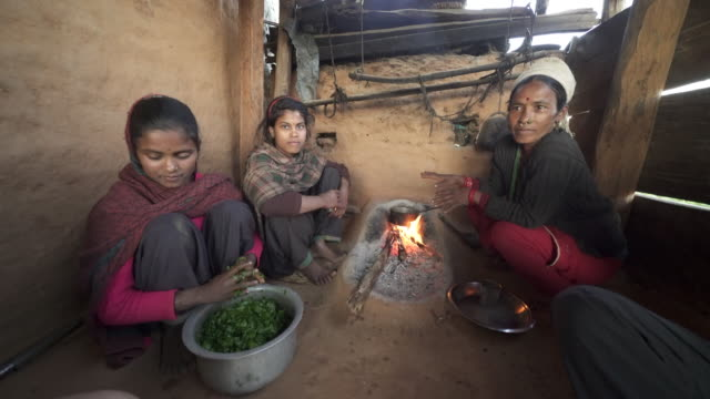 Nepali family prepares meal by small fire