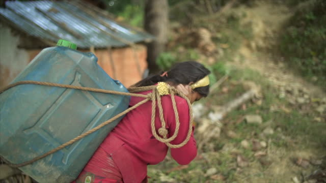 nepali girl carries large jug of water with head strap - povertà video stock e b–roll