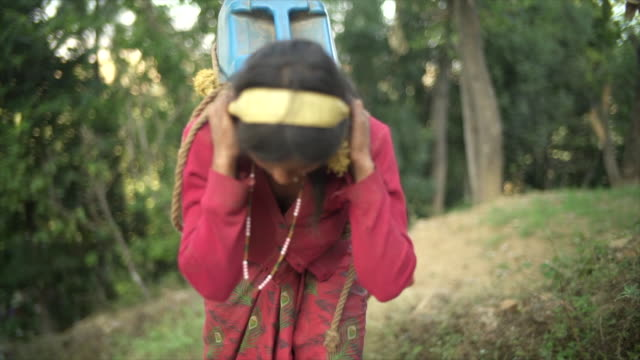 nepali girls carry large jugs of water uphill - portare video stock e b–roll