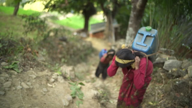 Nepali girls carry large jugs of water uphill