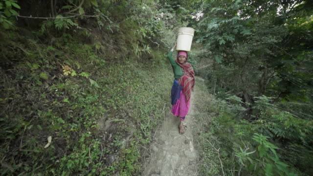 nepali woman carries plastic bucket on head on narrow dirt path - nepal stock videos & royalty-free footage