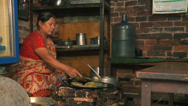 Nepali woman cooking food over a fire.