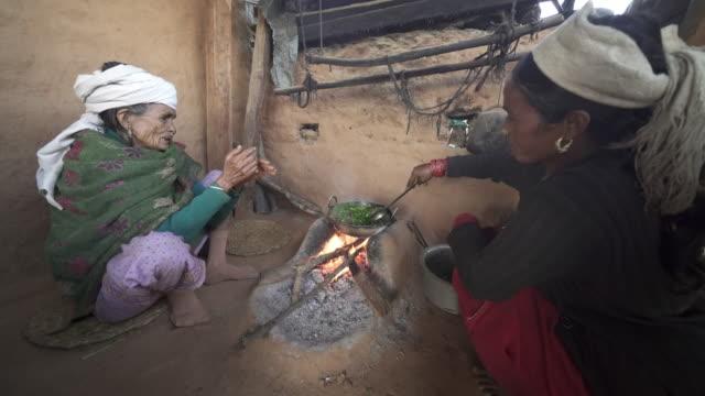 Nepali women prepare meal over fire