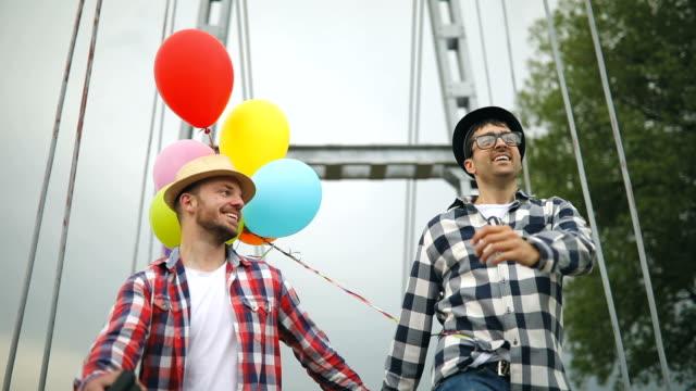 vídeos y material grabado en eventos de stock de pareja gay nerd que se divierten con los globos - homosexual