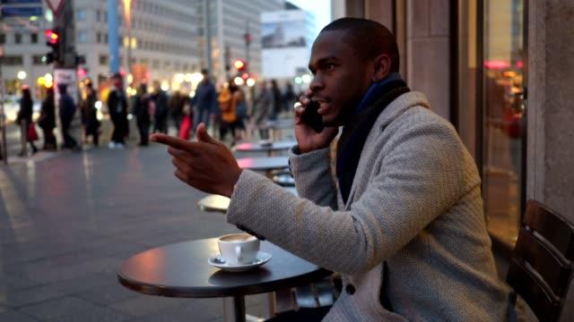 Nervösen Geschäftsmann telefonieren mit einem Handy beim Kaffeetrinken