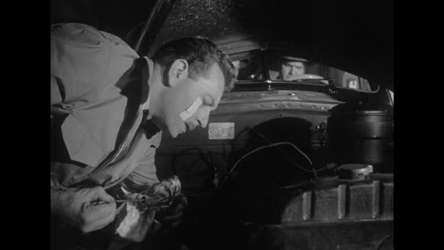 1948 nervous car mechanic works under car hood and avoids eye contact with men in car - petrol stock videos & royalty-free footage
