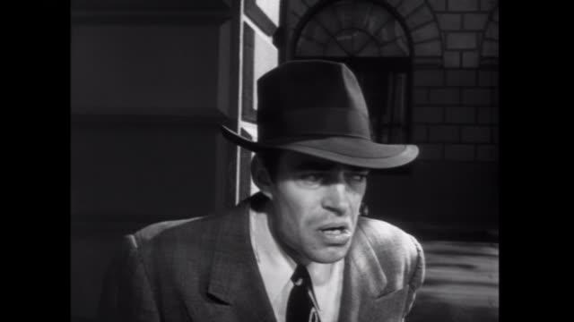 stockvideo's en b-roll-footage met 1952 a nervous gangster lights a cigarette in a phone booth - telefooncel