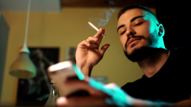 nervous man smoking cigarette and use phone - smoking issues stock videos & royalty-free footage