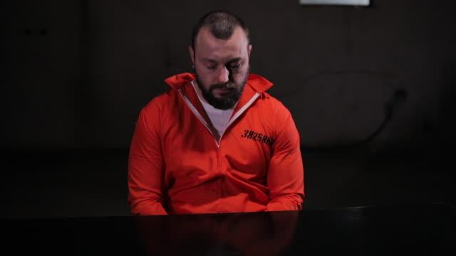 オレンジのジャンプスーツの神経質な囚人尋問室に一人で座っている - 捕らわれる点の映像素材/bロール