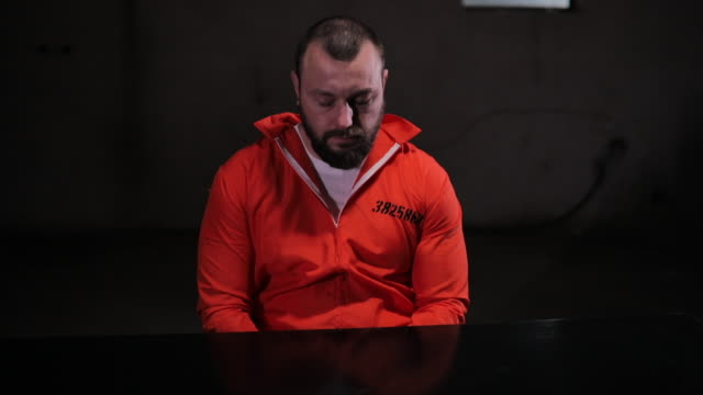 nervous prisoner in orange jumpsuit sitting alone in interrogation room - prisoner orange stock videos & royalty-free footage