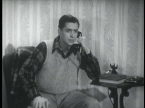 b/w 1947 nervous teenage boy talking on telephone / smiles + relaxes - one teenage boy only stock videos & royalty-free footage