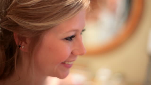 HANDHELD CLOSE UP nervous young bride smiles and nods before wedding