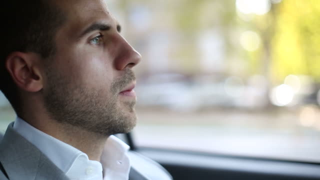nervous young businessman in a car - ingorgo stradale video stock e b–roll