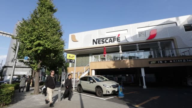 nestle sa's nescafe coffee shop stands in the harajuku district of tokyo, japan, on thursday, nov. 16 branded coffee mugs are displayed on a shelf... - human arm stock videos & royalty-free footage