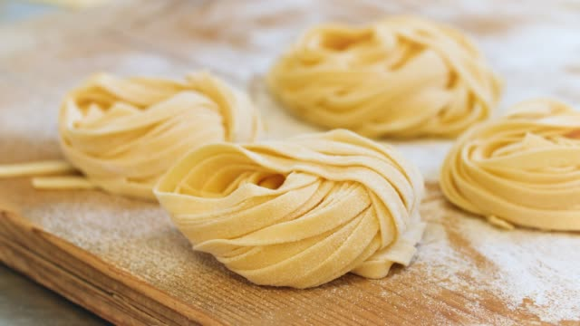 nests of tagliatelle lie on wooden board - tagliatelle stock videos and b-roll footage