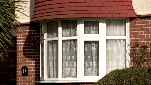 vídeos y material grabado en eventos de stock de net curtains hang across bay windows of a 1930s house in suburban london. available in hd. - ventana en saliente