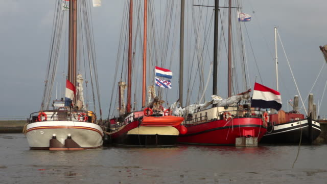 netherlands, ameland island, belonging to wadden sea islands. unesco world heritage site. former cargo sailing flatbottomed boats in harbour at low tide - mud flat stock videos and b-roll footage
