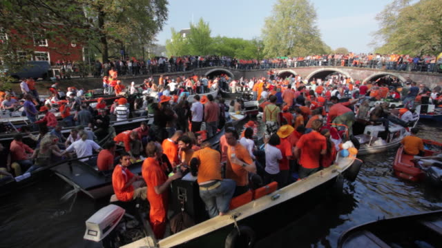 netherlands, amsterdam, canals full of boats during kingsday, an annual festival on 27 april. many people dressed in orange, the national color. - canal stock videos & royalty-free footage