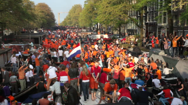 netherlands, amsterdam, canals full of boats during kingsday, an annual festival on 27 april. many people dressed in orange, the national color - canal stock videos & royalty-free footage