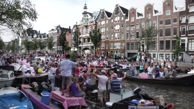 netherlands, amsterdam, canals full of boats during the gay parade, part of the annual gay pride festival. - amsterdam stock videos & royalty-free footage