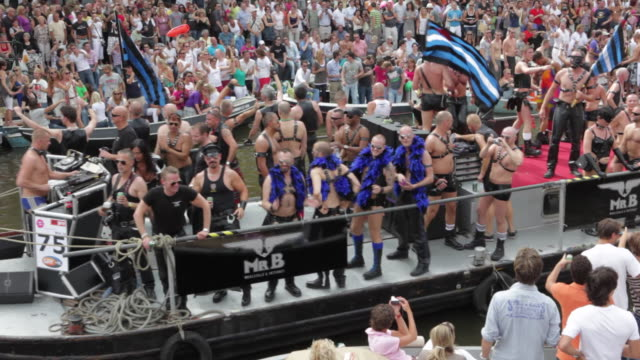 Netherlands, Amsterdam, Canals full of boats during the Gay Parade, part of the annual Gay Pride festival.