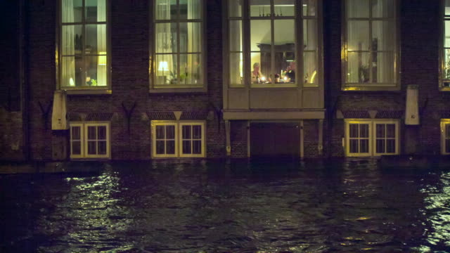 Netherlands, Dordrecht, Flood in historic inner city, Senior couple dines on first floor, while the basement is under water