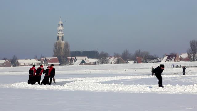 netherlands, hindeloopen. ice skating on frozen lake called ijsselmeer - niederlande stock-videos und b-roll-filmmaterial