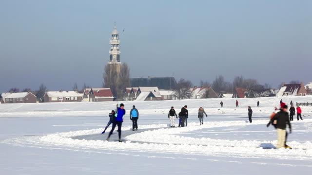 Netherlands, Hindeloopen. Ice skating on frozen lake called IJsselmeer