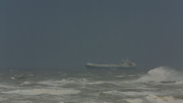 Netherlands, IJmuiden, Cargo ship arrives in harbor during heavy storm on North Sea