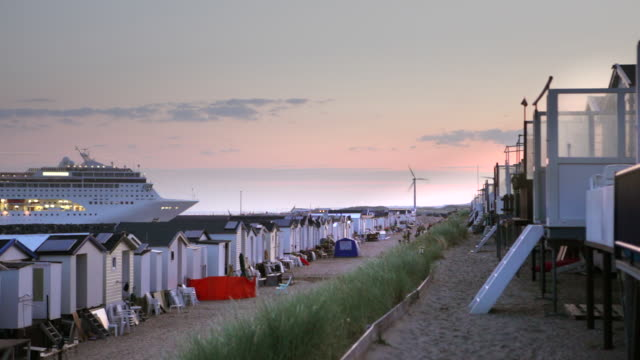 netherlands, ijmuiden, cruise ship enters north sea canal. foreground beach cabins - north sea canal stock videos & royalty-free footage