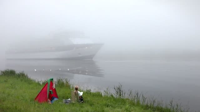 netherlands, ijmuiden, cruise-ship in north-sea-canal and woman reads book on shore. fog, mist - north sea canal stock videos & royalty-free footage