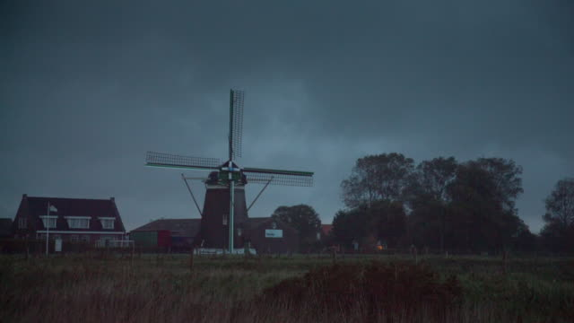 netherlands, kerkwerve, windmill in rain and storm. dusk - idyllic stock videos & royalty-free footage