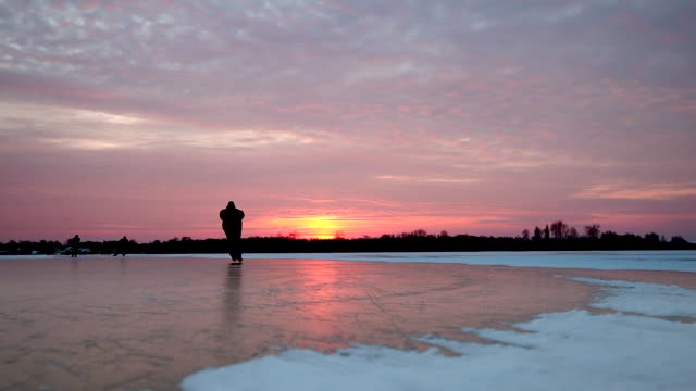 netherlands, loosdrecht, people ice skating on lake called loosdrechtse plassen, sunrise - ice skating stock videos & royalty-free footage
