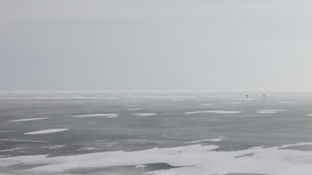 netherlands, marken, frozen lake called ijsselmeer. two isolated ice skaters - olanda settentrionale video stock e b–roll