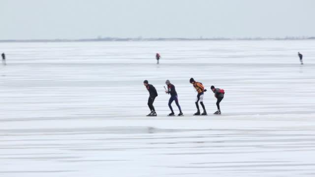 Netherlands, Marken, People ice skating on lake called Gouwzee, part of lake called IJsselmeer