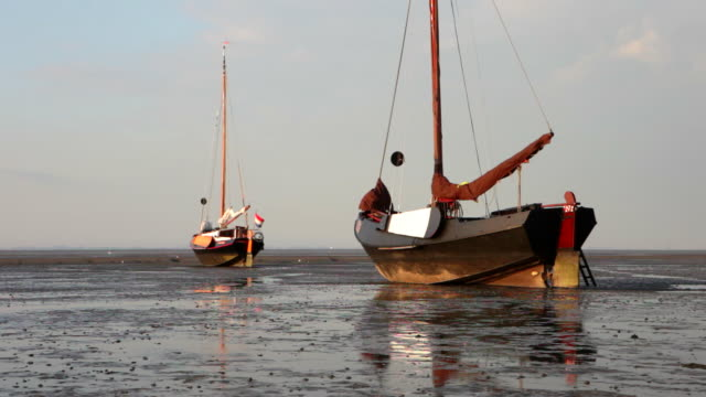 netherlands, nes on ameland, island belonging to wadden sea islands. boats on mud flat at low tide - mud flat stock videos and b-roll footage