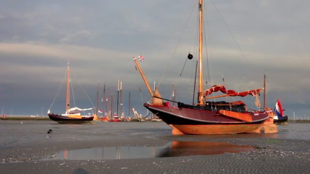 Netherlands, Nes on Ameland, Island belonging to Wadden Sea Islands. Boats on mud flat at low tide