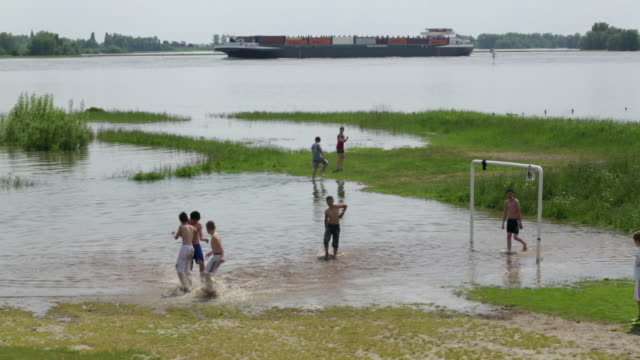 netherlands, ochten, boys playing football in the flooded flood plains of the waal river due to high water, background inland waterway vessels - soccer goal stock videos and b-roll footage