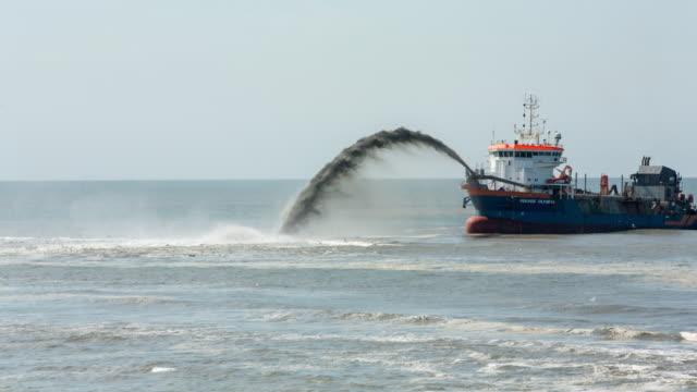 Netherlands, Petten, Reinforcement of sea dike called Hondsbossche Zeewering. A Trailing Suction Hopper Dredger is depositing sand in front of the dyke