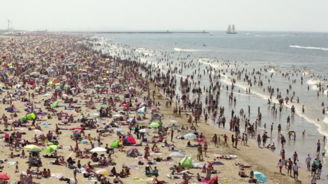 netherlands, scheveningen, near the hague, summertime on the beach, people sunbathing and enjoying the sea water - trång bildbanksvideor och videomaterial från bakom kulisserna