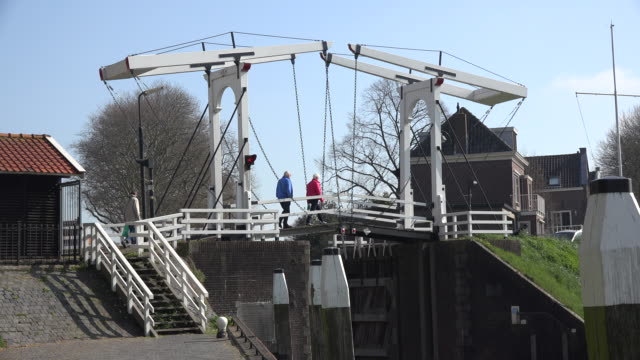 vídeos de stock, filmes e b-roll de netherlands schoonhoven three people cross drawbridge - drawbridge