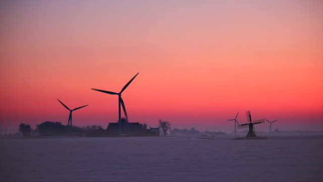 netherlands, tritzum, small traditional windmill and modern wind turbines and farm in snow at sunset - dusk bildbanksvideor och videomaterial från bakom kulisserna