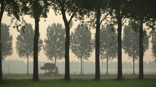 Netherlands, Vijfhuizen, Amsterdam Schiphol Airport, Runway called Polderbaan, KLM airplane landing, Farmer working on land with tractor, Cyclist