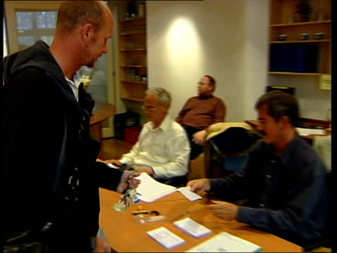 netherlands vote in european constitution referendum amsterdam male voter into polling station and up to registration table cms voting slip handed... - olanda settentrionale video stock e b–roll