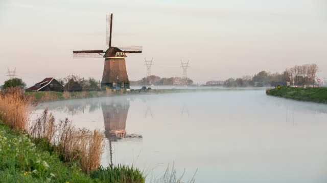 netherlands, wijdewormer, windmill along belt canal of beemster polder, a unesco world heritage site - polder stock videos and b-roll footage