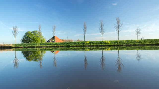 netherlands, zuidoostbeemster, farm near belt canal of beemster polder, a unesco world heritage site. cyclist - olanda settentrionale video stock e b–roll