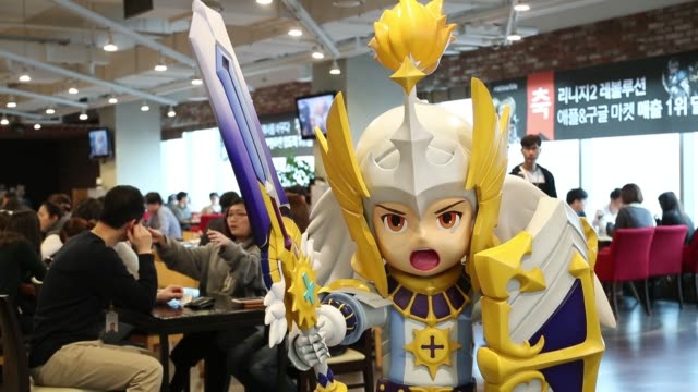 A Netmarble Games Corp employee walks past a model figure of Rudy a character from the Seven Knights mobile roleplaying game in the cafeteria of the...